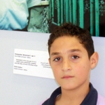 "Mohammed, proudly in front of his photo at the ""Suwarna"" Exhibition"