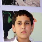 "Taha, proudly in front of his photo at the ""Suwarna"" Exhibition"
